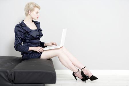 Beautiful young woman working on laptop in a smart business suit.