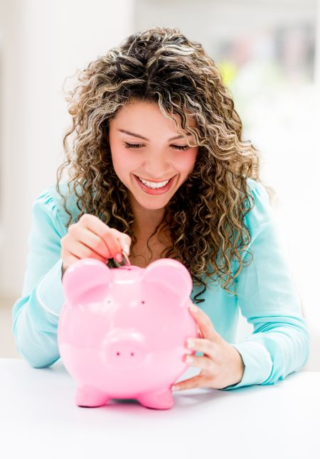 Happy woman putting savings in a piggybank
