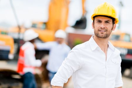 Male engineer working at a construction site and wearing helmet