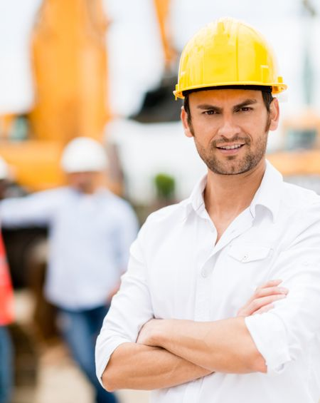 Male architect with arms crossed working at a construction site