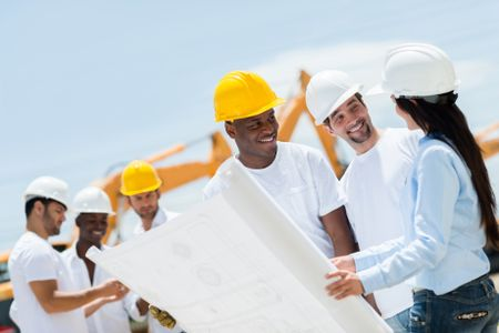 Architect at a construction site looking at blueprints with workers