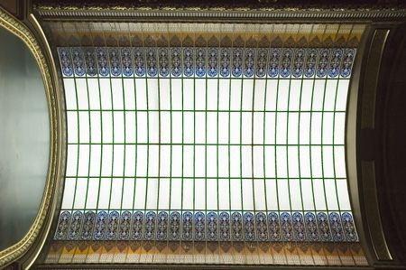 Skylight with stained glass above mural with gilded frame in state capitol building