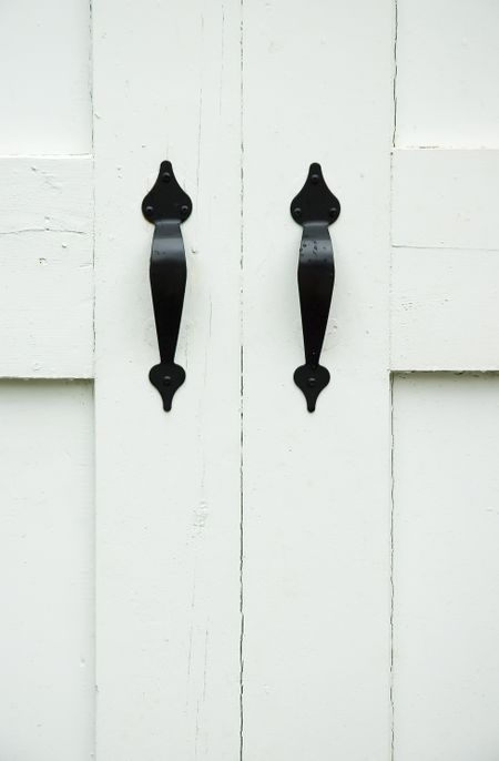 Two black iron handles with a few raindrops on white wooden doors