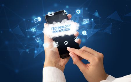 Female hand holding smartphone with TECHNOLOGY INNOVATION inscription, cloud technology concept