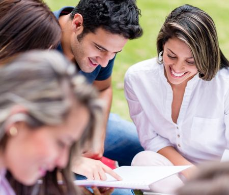 Group of students outdoors studying together and smiling