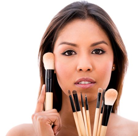 Beautiful woman with make up brushes - isolated over a white background