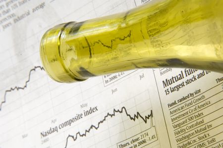 Neck of wine bottle above financial page of newspaper