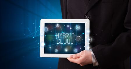 Young business person working on tablet and shows the digital sign: HYBRID CLOUD