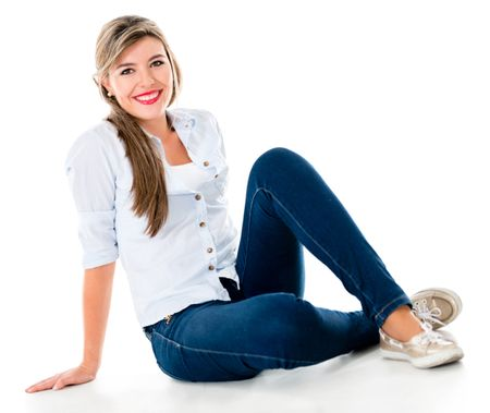 Casual woman sitting on the floor smiling - isolated over a white background