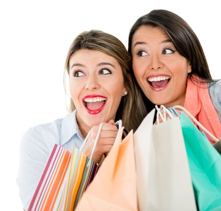 Surprised shopping women holding bags - isolated over a white background