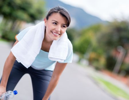 Fit woman resting while running in the city and smiling