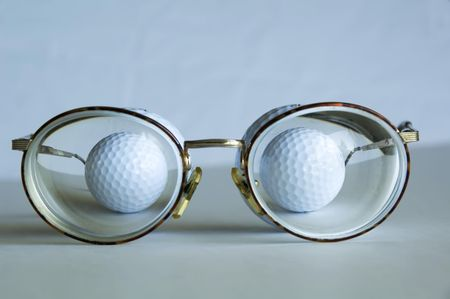 Two golf balls behind thick lenses of eyeglasses