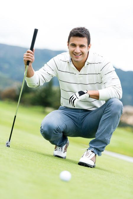 Male golf player at the course holding a club