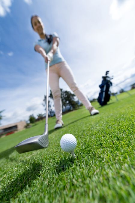 Woman playing golf at the course - focus on ball