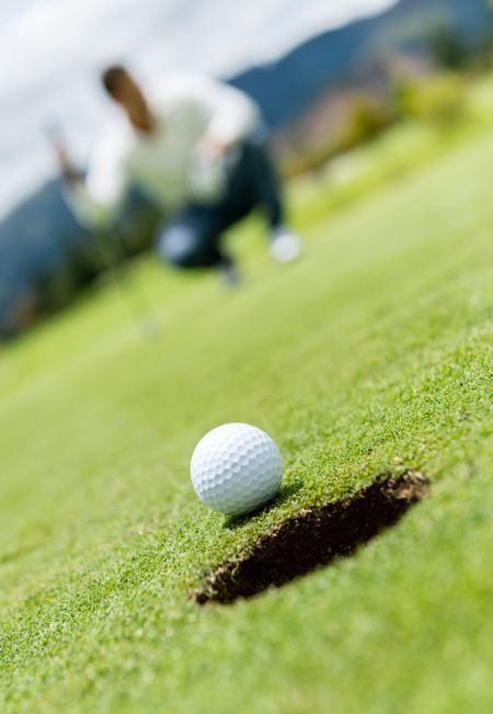 Golf ball very close to going into a hole