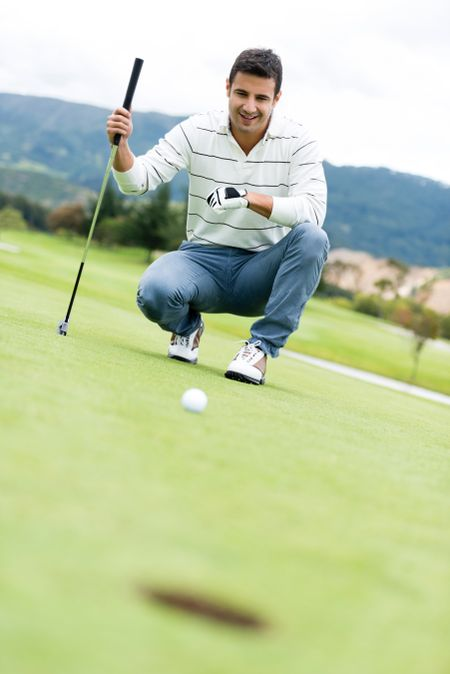 Man playing golf looking at the ball going into a hole