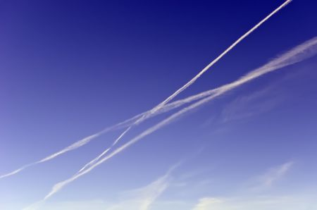 Travel concept of intersecting journeys: Three contrails crisscrossing while another dissipates across blue sky