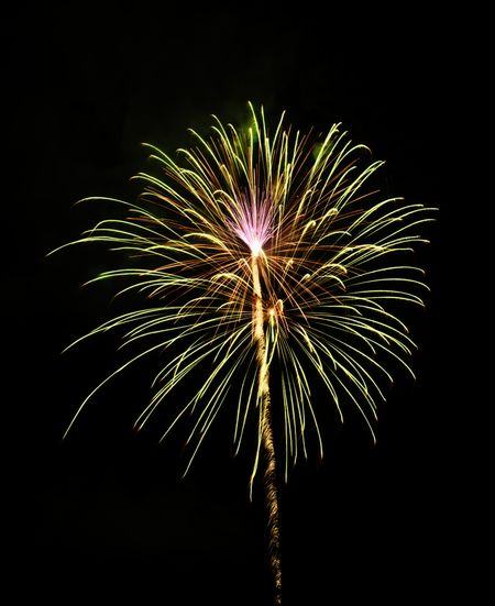 Yellow-green burst of fireworks with a pink flowery effect at its core