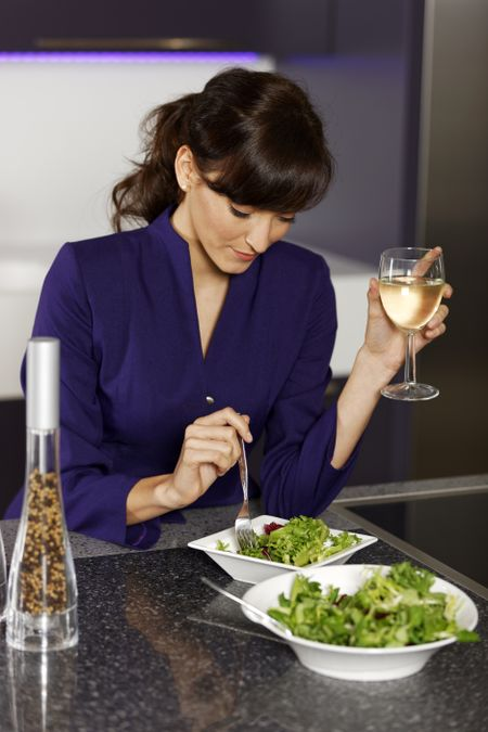 Attractive young woman preparing a healthy lunch after work.