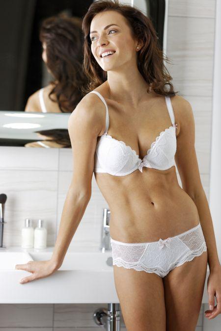 Attractive young woman in underwear standing in her modern bathroom