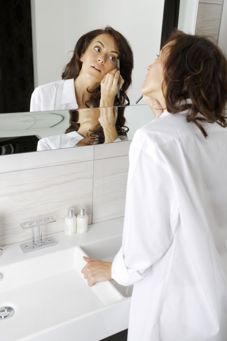 Attractive young woman doing her makeup in front of the bathroom mirror.
