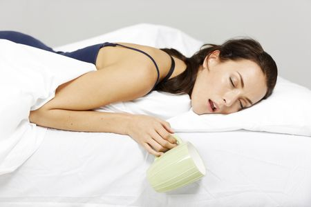 Young woman falling asleep in bed with drink in hand
