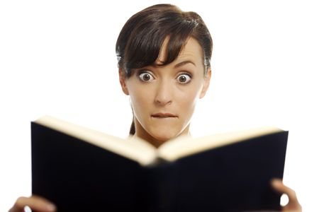 Young woman reading a scary book
