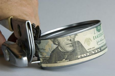 Man's hand using can opener to open a can of money