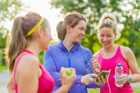Group of happy active girls preparing for a run in nature by choosing music on a smart phone
