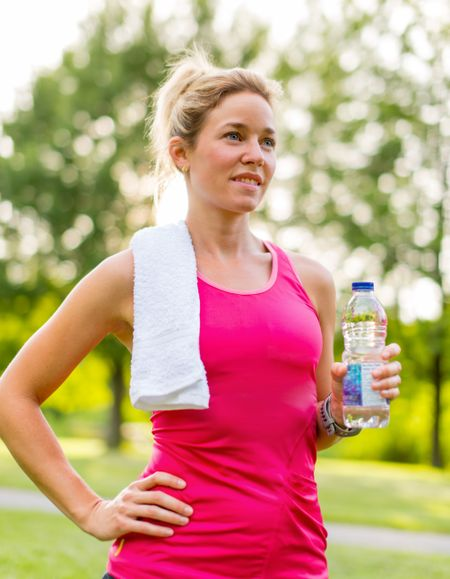 Portait of a beautiful active girl keeping hydrated by drinking water during her workout under trees