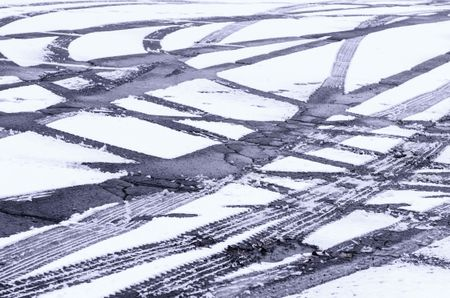 Winter at a glance: Fresh tire tracks intersecting in light snow on asphalt pavement of parking lot