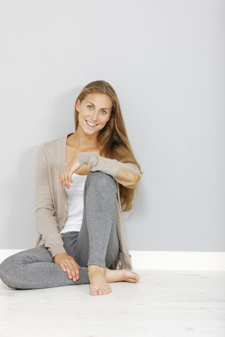 Attractive young woman sitting on the floor at home relaxing