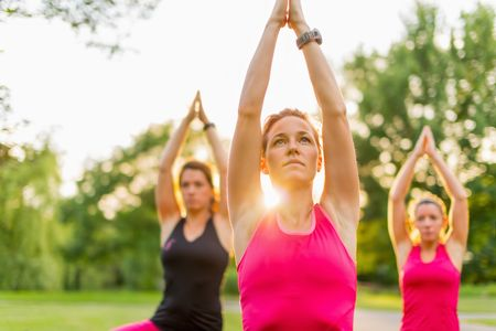 horizontal detail of women doing yoga outdoors at sunset with lens flare. Defocused