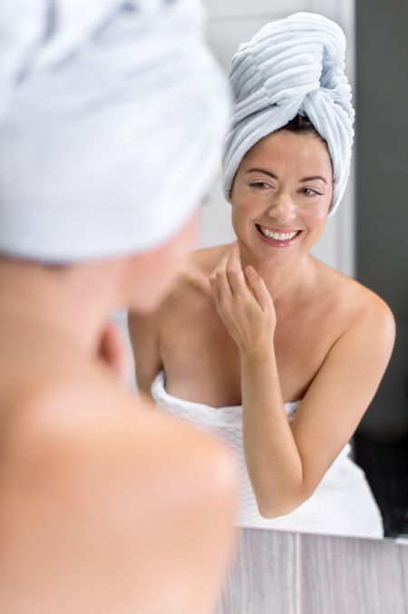 Attractive middle aged woman looking in the mirror