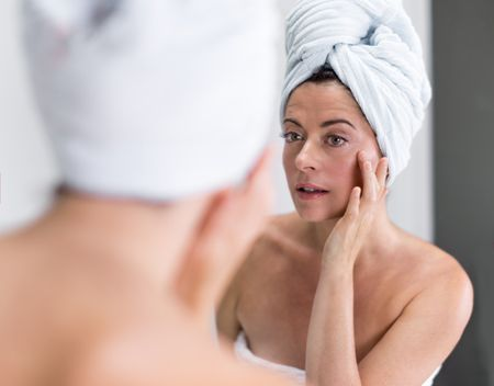 Middle aged woman looking at herself in the mirror