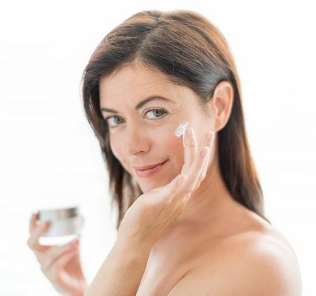 attractive woman in her forties applying cream