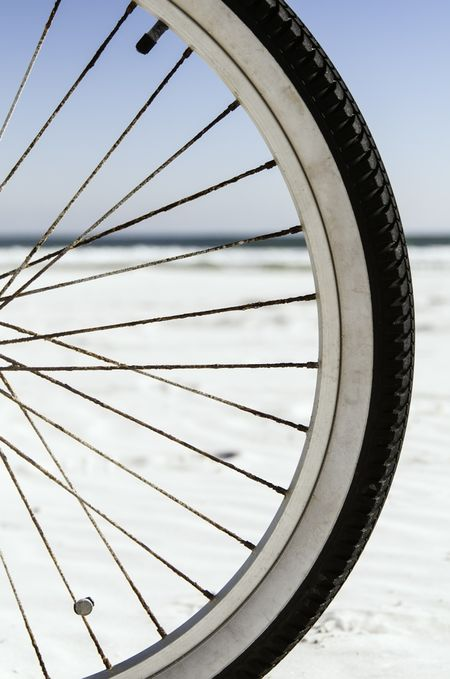 Mobility at the beach: Focus on front tire of bicycle, with horizon of Atlantic Ocean in background (shallow depth of field)