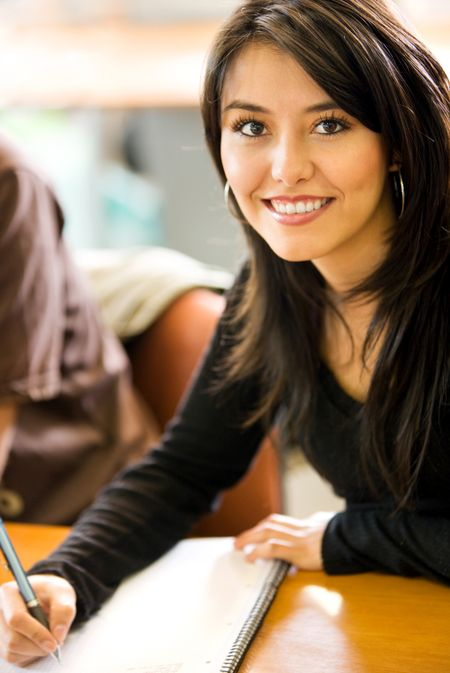Beautiful girl studying in a classroom - smiling and writting on her notebook