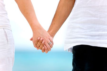 couple holding hands by the sea in a romantic setting