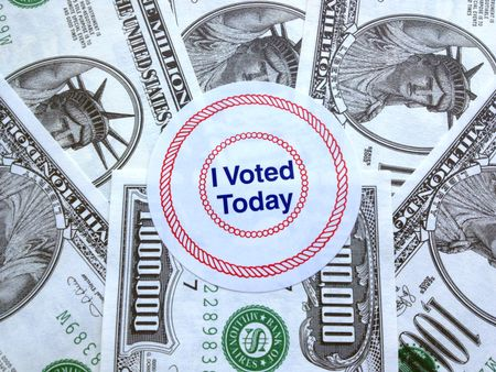 It pays to vote: Proclamatory sticker on a pile of fake million-dollar bills (play money)