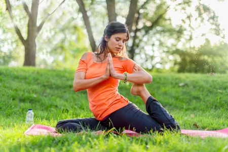 Active woman doing yoga poses at sunset