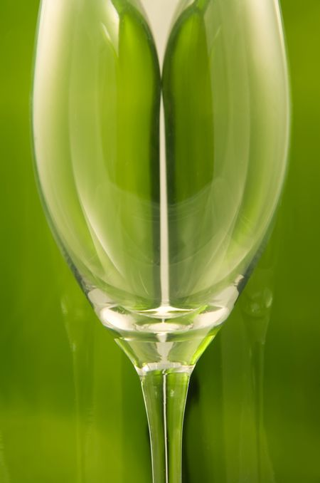 Wine glass in front of two green wine bottles