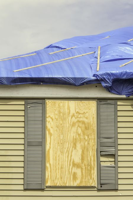 House repairs after tornado: Boarded window beneath roof with protective sheets of blue plastic