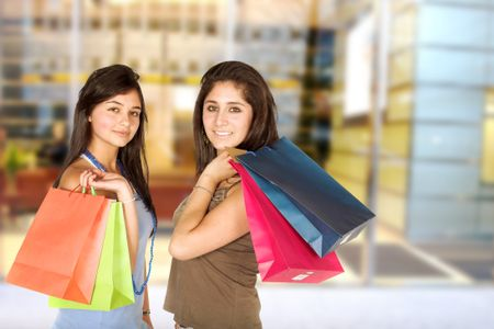beautiful teenagers with shopping bags over white