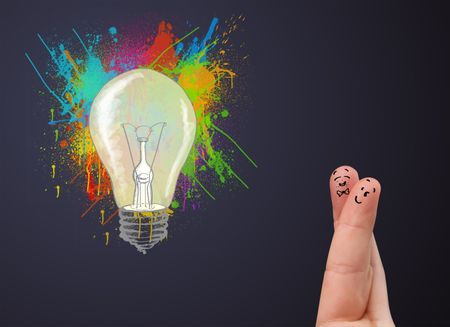 Happy cheerful smiley fingers looking at abstract hand drawn colorful lightbulb