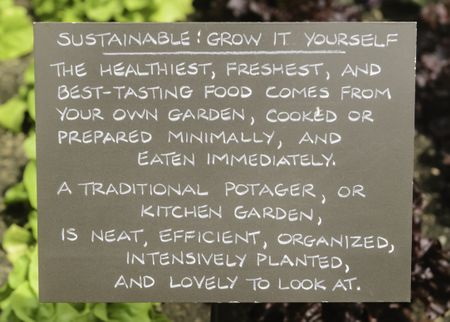 Encouragement for potential gardeners: Sustainability sign by rows of vegetables in botanic garden