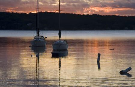 Two sailboats at anchor near shore at dawn