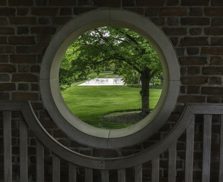 Outside world at a glance: Four-part porthole in a walled garden with a view of spacious green lawn, trees, and patio across the way