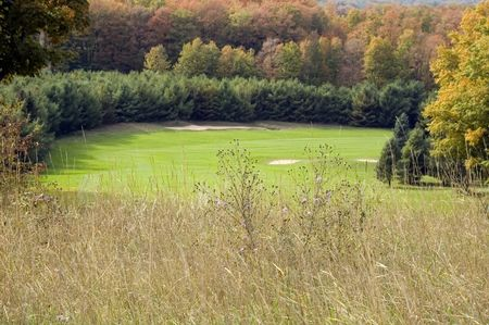 Dogleg with bunkers on golf course in northern woods in autumn