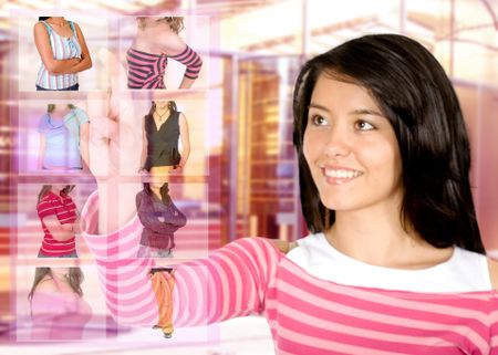 clothes shopping online - girl inside a retail clothes store choosing their favourite item on screen - focus is on the finger and clothes buttons